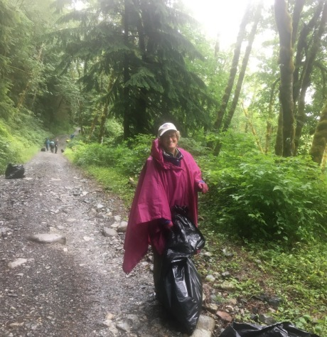 Volunteer bagging up invasive plants pulled on the Middle Fork Road-Trail on a rainy day. Photo by Joe Neumann.
