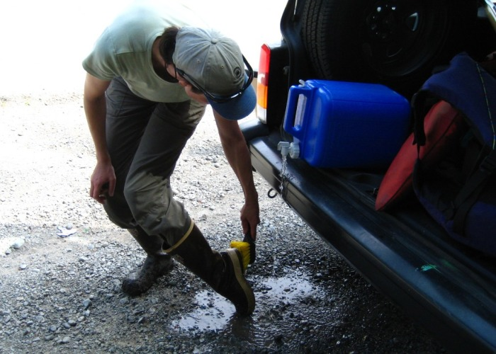 Washing mud off boots with water and a brush to stop weeds from spreading.