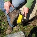 Brushing dirt off of boots to prevent spread of weeds
