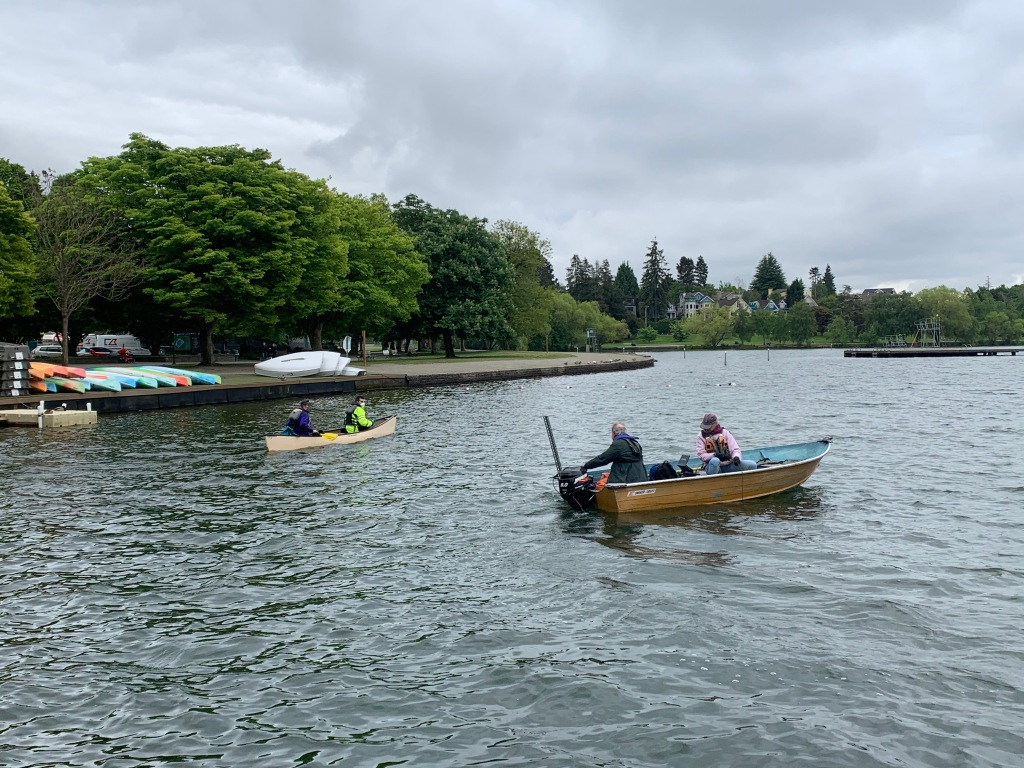 A canoe and a small motorboat each with two people on a lake
