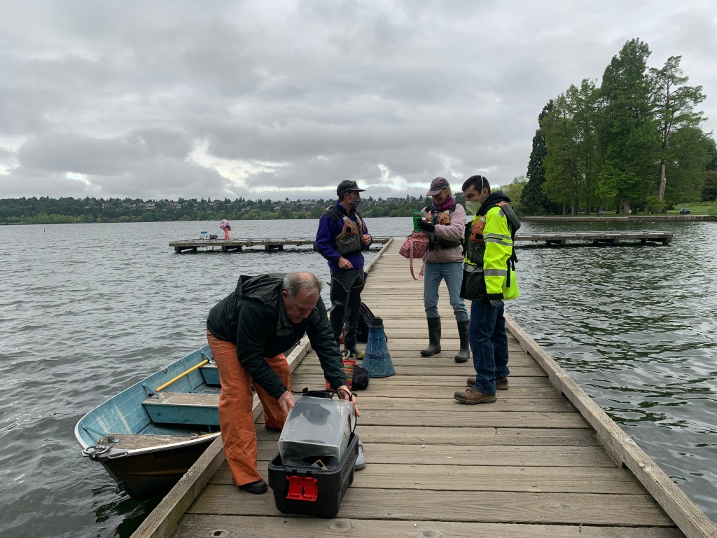 Four people on a dock get ready to survey for Egeria in Green Lake